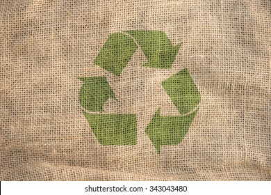 Recycle symbol on rough textile fabric. Concept of environment, recycling and eco awareness.