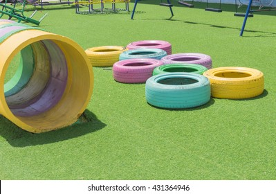 "Recycle Tire for Recreation Safety Playground on Artificial Grass Field,School grass field with reused Wheel rubber,Color Cement Pipes on field ,Reuse Tire for ""Add Value"" Concept."