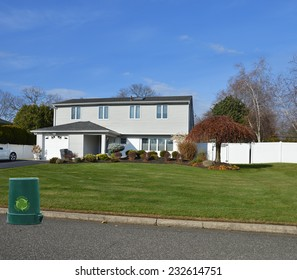 Recycle trash container suburban high ranch style home autumn season residential neighborhood blue sky USA