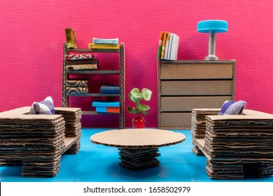 Recycled cardboard dollhouse furniture. Two couches, a table a cupboard and a book case with miniature books. On a blue floor and a pink wall.