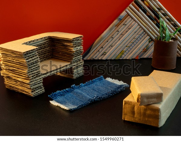 Recycled corrugated cardboard couch for a doll house with cardboard boxes and reused denim rug on a dark floor. Red wall. Room for copy.