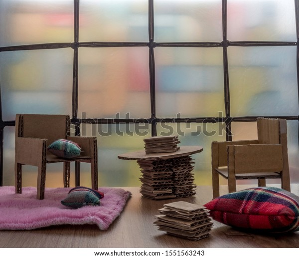 Recycled corrugated cardboard dollhouse furniture. With stained glass window, a pink rug and cushions. Room for copy.