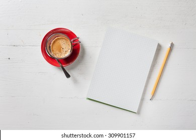 A recycled paper notebook checked with a black pencil with the eraser at the top and a cup of coffee with red saucer and spoon, are arranged on a wooden table painted white. View from the top