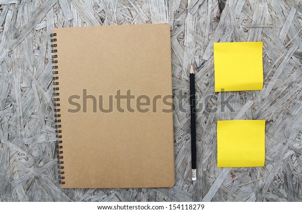 Recycled paper notebook front cover on wood background