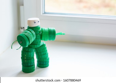 Recycling art. Zero waste, the second life of things. Toy robot made of plastic caps on the window. copyspace