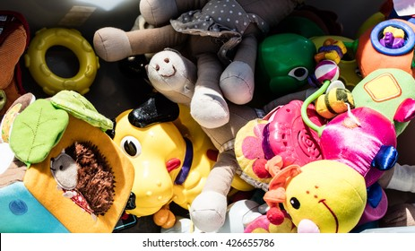 recycling baby toys and teddies made of cheap plastic or fabric in bulk display at garage sale of flea market for over-consumption society, outdoors