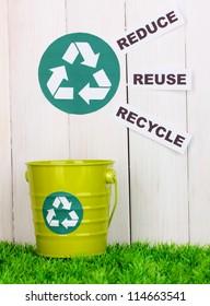 Recycling bin on green grass near wooden fence