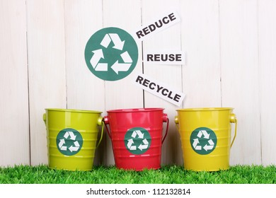 Recycling bins on green grass near wooden fence