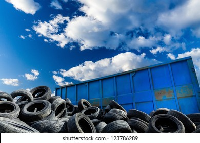Recycling business with metal container and car tires over blue sky. Ecology and recycle industry, saving nature and environment.
