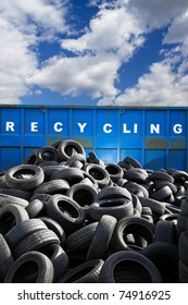 Recycling container and car tires, landfill over blue cloudy sky