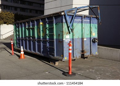 A recycling dumpster is placed outside with caution cones in a sunny day