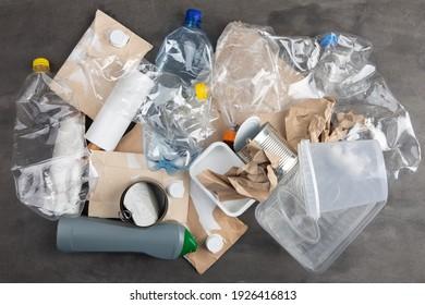 Recycling und Ökologie-Konzept. Sortieren von Haushaltsabfällen, die von oben erfasst werden, flach gelegt. grauer Beton, Hintergrund