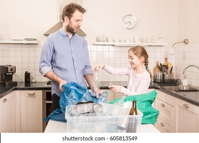 Recycling and ecology - happy caucasian family (father and daughter) sorting (segregating) household waste in the kitchen. Lifestyle - ecological education and awareness concept.