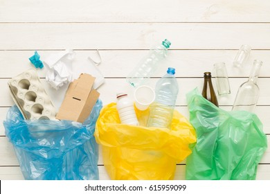 Recycling and ecology. Sorting (segregating) household waste (paper, glass, plastic) into bags captured from above (flat lay). White wooden background with free text (copy) space.