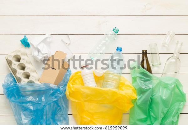 Recycling en ecologie. Sorteren (scheiden) huishoudelijk afval (papier, glas, plastic) in zakken die van bovenaf worden gevangen (plat leggen). Witte houten achtergrond met vrije tekst (kopie) ruimte.