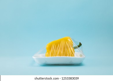 Recycling and environment concept: fresh food in plastic package. Yellow bell pepper wrapped in plastic clingfilm in blue background.