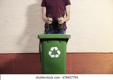 Recycling glass bottles / Man holding two green glass bottles over recycle bin outdoors  copy space