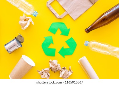 Recycling. Green recycle eco symbol. Recycled arrows sign near matherials for recycle and reuse on yellow background top view