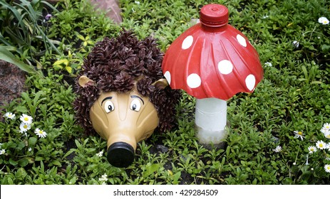 Recycling: a hedgehog and a mushroom made of plastic bottles in a garden