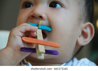 Recycling kid toy on baby hand.Handmade plane made from wooden cloth clamp and ice cream stick,dye with food coloring.Selective focus.
