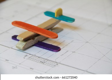Recycling kid toy put on baby engineering design drawing.Handmade plane made form wooden cloth clamp and ice cream stick,dye with food coloring.Selective focus.