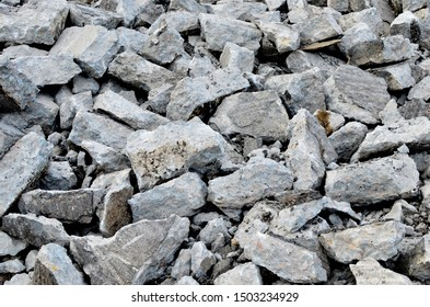Recycling and reuse crushed concrete rubble, asphalt, building material, blocks. Broken concrete slabs at construction site. Сoncrete rubble from demolition at landfill. Hardcore waste recycling