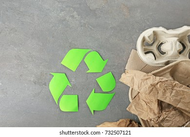 Recycling sign and garbage on textured background
