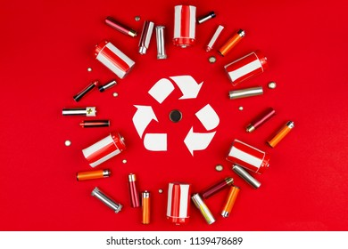 Recycling sign surrounded colorful AA batteries isolated on red background. Renewable / green energy concept. Safe environment / ecoly of planet