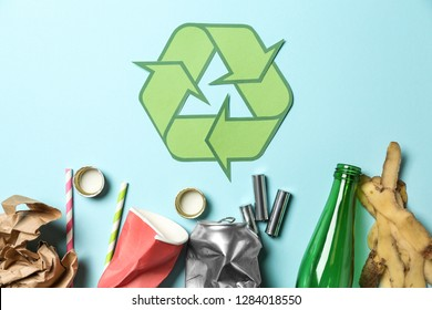 Recycling symbol and different garbage on color background