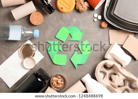 Recycling symbol and different garbage on gray background, top view