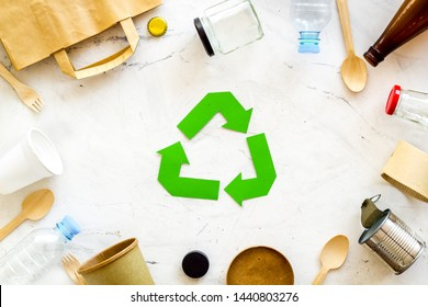 Recycling symbol and different garbage, paper bag, cup, flatware, plastic bottle for ecology marble background top view