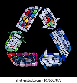 Recycling symbol made from colorful plastic bottles trash - ecology concept, isolated on black