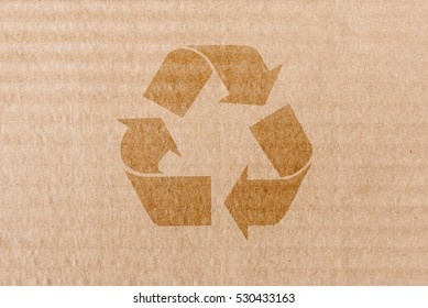 Recycling symbol on brown cardboard packing box. Concept of eco awareness, paper reuse and green thinking.