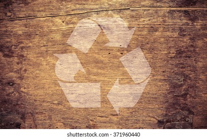 Recycling symbol on brown grungy wooden background texture. Concept of environment, reuse and green thinking.
