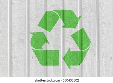 Recycling symbol on white wooden wall background. Concept of environment, reuse and green living.
