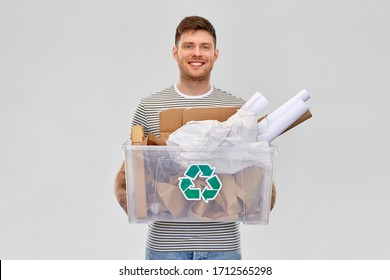 recycling, waste sorting and sustainability concept - smiling young man in striped t-shirt holding paper garbage in plastic box over grey background