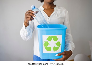 Recycling, waste sorting and sustainability concept - smiling young woman holding box with plastic bottles over grey background. Woman hand holdging box garbage for recycle