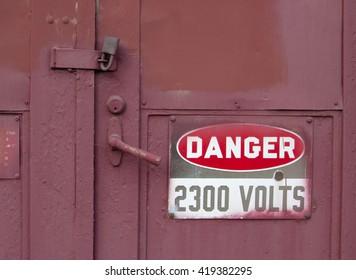 Red 2300 volts danger sign on red locked steel door.