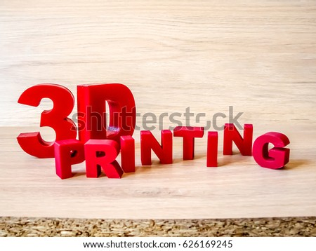 "Red 3d-printed letters ""3D printing"" on a wood board as background."