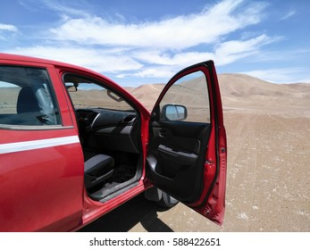 Red 4x4 with open front door and view to the desert