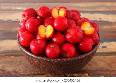 Red acerola - malpighia glabra, tropical fruit  in bowl on table. Selective focus
