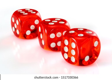 Red acrylic transparent dice for games. Three gambling translucent dices on white background, macro close up high resolution.