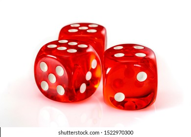 Red acrylic transparent dice for games. Three gambling translucent dices on white background, close up high resolution.