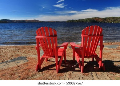 Red Adirondack chairs on Dwight Beach by Lake of Bays, Algonquin Highlands, Canada