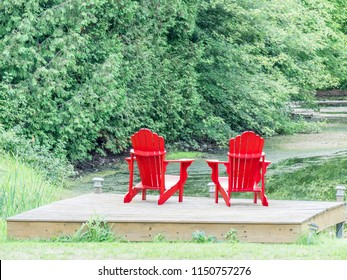Red Adirondack chairs on a wooden deck at a woodland pond