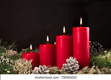 red advent candles with green pir and pinecone