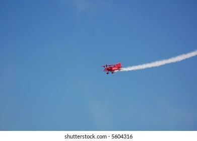 Red Aerobatic Biplane Performing Stunts