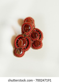 Red agate earrings overlapping isolated on white paper