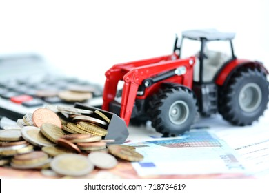 Red agricultural tractor, cash money and calculator suggesting professional financial support