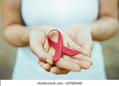 red aids ribbon in hand. soft focus on ribbon.